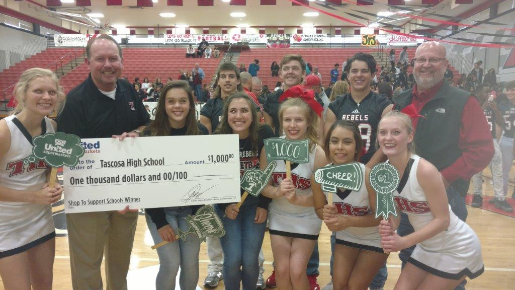 Market Street store director Matt Edwards celebrates Tascosa High School's Shop to Support Schools win with the THS cheerleaders.